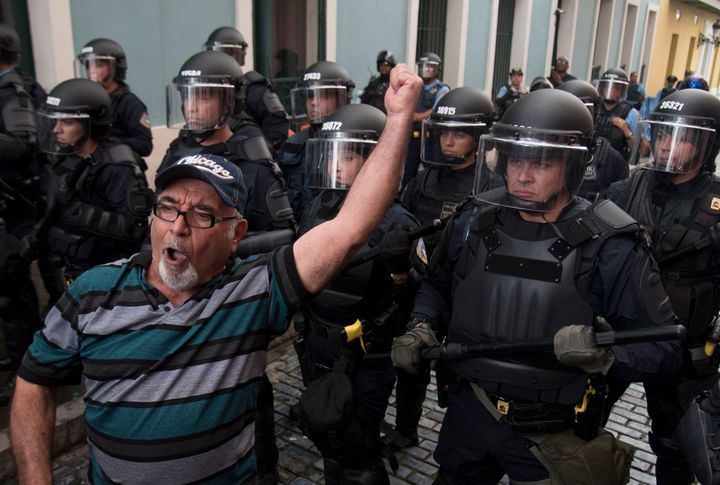 Police block demonstrators from advancing to La Fortaleza governor's residence in San Juan, Puerto Rico, Sunday, July 14, 201