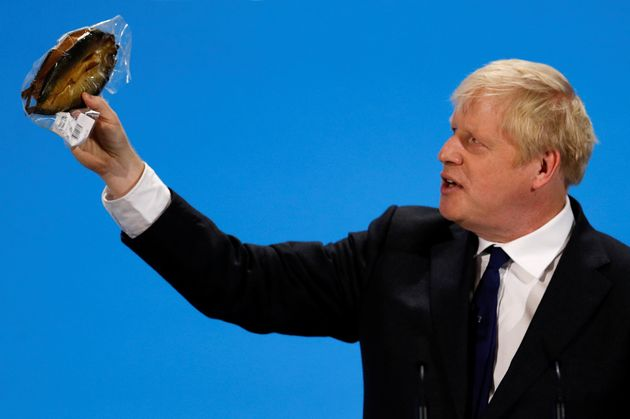 Boris Johnson, a Tory leadership candidate, holds a plastic wrapped kipper fish during a hustings event...