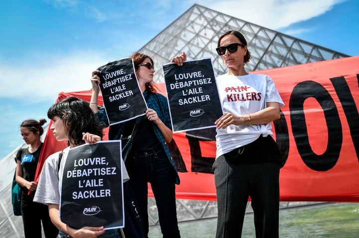 "Protesters hold banners reading ""Shame on Sackler"" and ""Take down the Sackler name"" in front of the Pyramid of the Louvre Mus"