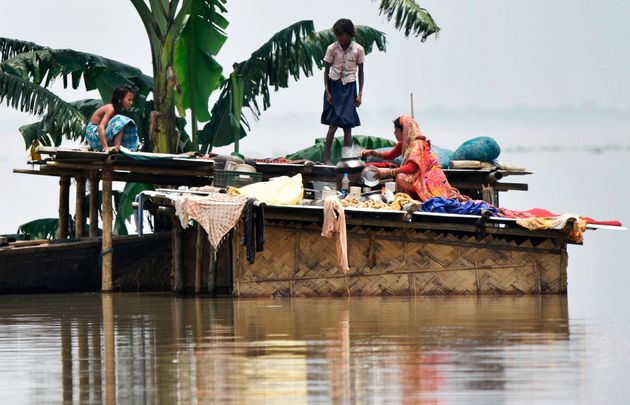 Members of a family stand atop a hut at the flood-affected area of Hatishila in Kamrup district of Assam...