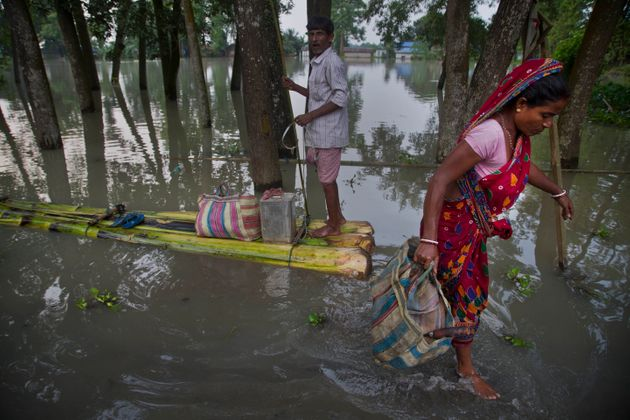 Woman gets down from a makeshift banana raft to collect relief materials in Jhargaon, east of Guwahati,...