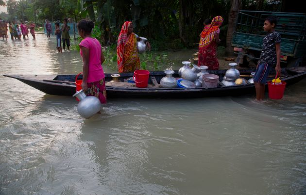 Flood-affected villagers stand near a boat filled with vessels of drinking water in Jhargaon, east of...