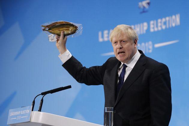 Boris Johnson brandit un hareng fumé lors d'un meeting conservateur à Londres le 17 juillet