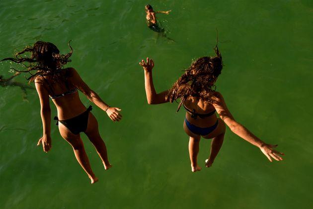 Dos chicas saltan desde una plataforma a las aguas de La Concha, en San Sebastián, el pasado