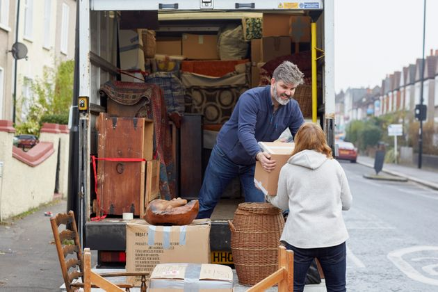 A man and a woman load a moving truck with