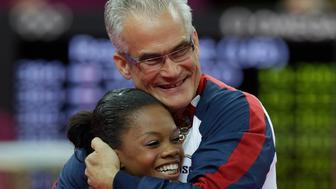 U.S. head coach John Geddert hugs gymnast Gabrielle Douglas after her performance during the Artistic Gymnastics women's team final at the 2012 Summer Olympics, Tuesday, July 31, 2012, in London. (AP Photo/Julie Jacobson)