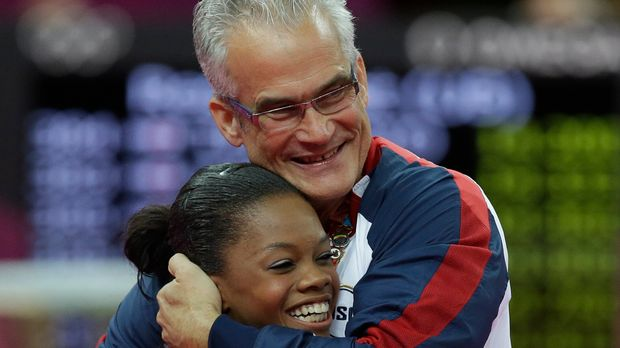 U.S. head coach John Geddert hugs gymnast Gabrielle Douglas after her performance during the Artistic Gymnastics women's team final at the 2012 Summer Olympics, Tuesday, July 31, 2012, in London. (AP Photo/Julie Jacobson)