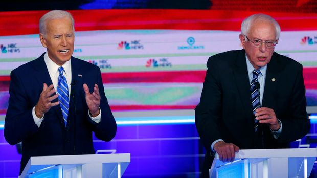 In this June 27, 2019, photo, Democratic presidential candidates former vice president Joe Biden and Sen. Bernie Sanders, I-Vt., speak at the same time during the Democratic primary debate hosted by NBC News at the Adrienne Arsht Center for the Performing Arts in Miami. (AP Photo/Wilfredo Lee)