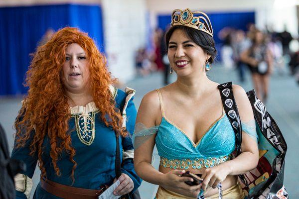 Cosplayers dressed as Princess Merida, left, and Princess Jasmine.