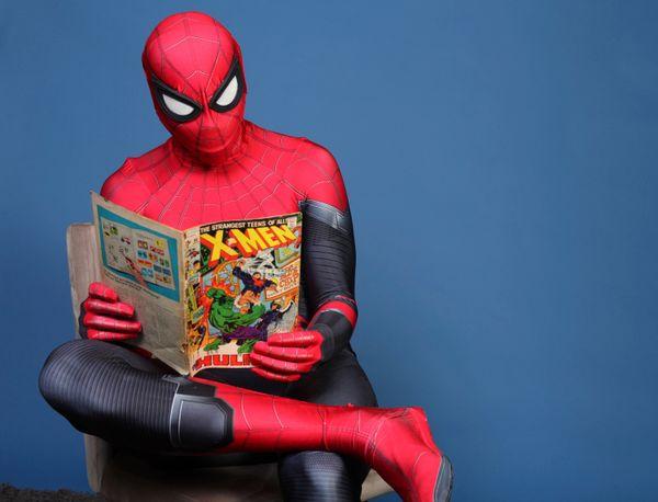 Evan Nuzum reads a comic book dressed as Spider-Man.