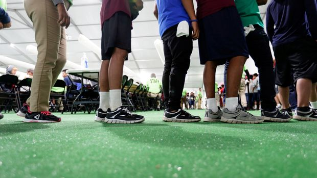 Immigrants line up in the dinning hall at the U.S. government's newest holding center for migrant children in Carrizo Springs, Texas, U.S. July 9, 2019.     Picture taken July 9, 2019.      Eric Gay/Pool via REUTERS