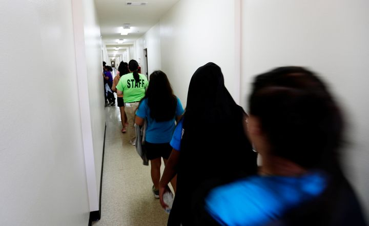 Immigrants walk down the hall of a dormitory at the U.S. government's newest holding center for migrant children in Carrizo S