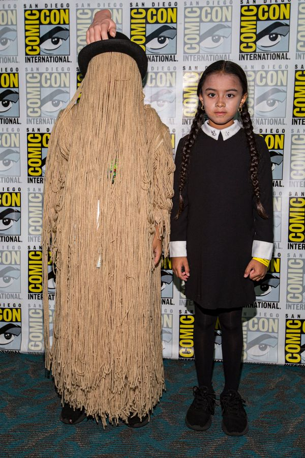 "Young cosplayers Ron Pizarro (L) and Mya Pizarro dressed as Cousin It and Wednesday Addams from ""The Addams Family."""