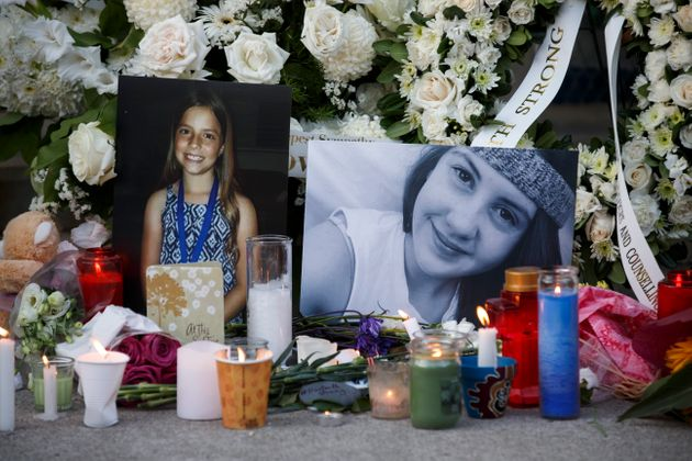 Photos of victims Julianna Kozis, 10, left, and Reese Fallon, 18, are seen during a vigil for victims...