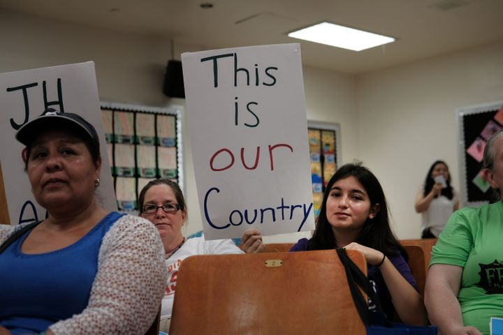 Some of Ocasio-Cortez's diverse constituents brought homemade signs to an immigration town hall on Saturday.