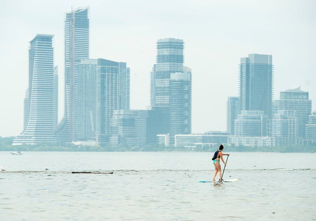 A women paddle boards along Lake Ontario during an extreme heat alert in Toronto on July 19,