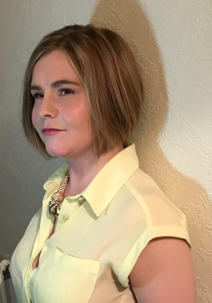 A side-shot of Sassy Wyatt in a yellow blouse wearing a gold necklace. She has short blond hair and is looking directly at the camera and smiling.