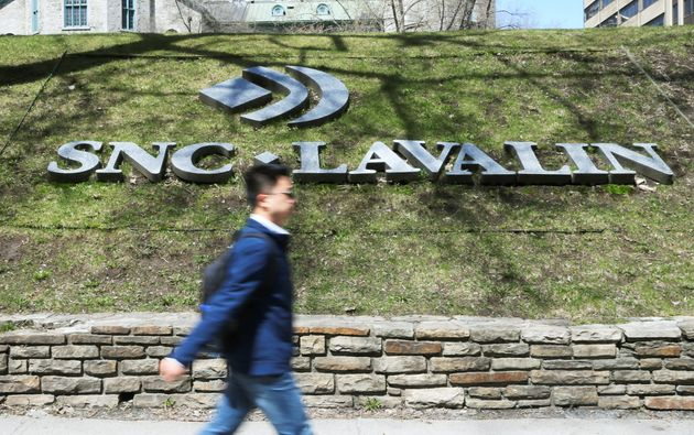 A pedestrian walks past the SNC-Lavalin logo outside the company headquarters building in Montreal, May