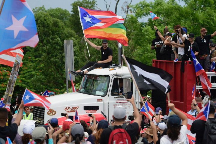 Ricky Martin, holding a Puerto Rican flag and a rainbow banner, joins thousands of Puerto Ricans for what many are expecting
