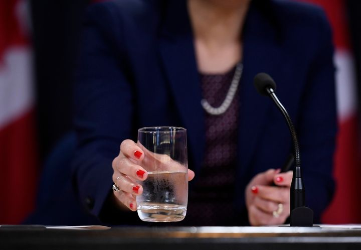 Health Minister Ginette Petitpas Taylor drinks from a glass of water during a press conference at the National Press Theatre in Ottawa on July 22, 2019.