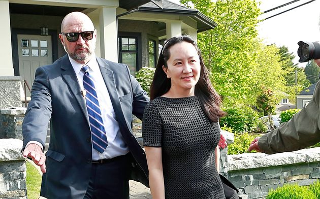 Huawei Technologies Chief Financial Officer Meng Wanzhou is escorted by security from her home in Vancouver...