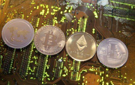 Representations of the Ripple, Bitcoin, Etherum and Litecoin virtual currencies are seen on motherboard...