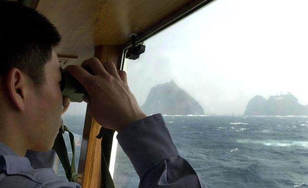 Sur cette photo d'archives datant de 2005, un garde-côtier sud-coréen regarde à travers...