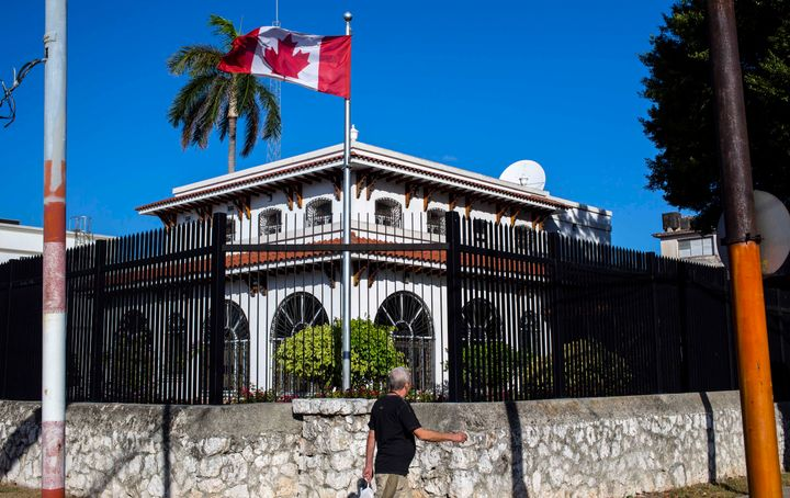 In this April 17, 2018 file photo, a man walks beside Canada's embassy in Havana, Cuba. Some Canadian diplomats who became my