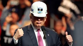 Republican presidential candidate Donald Trump puts on a miners hard hat during a rally in Charleston, W.Va., Thursday, May 5, 2016. (AP Photo/Steve Helber)