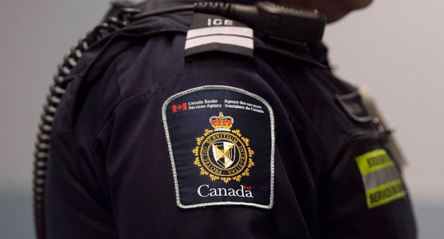 A Canada Border Services agent stands watch at Pearson International Airport in Toronto on Dec. 8,