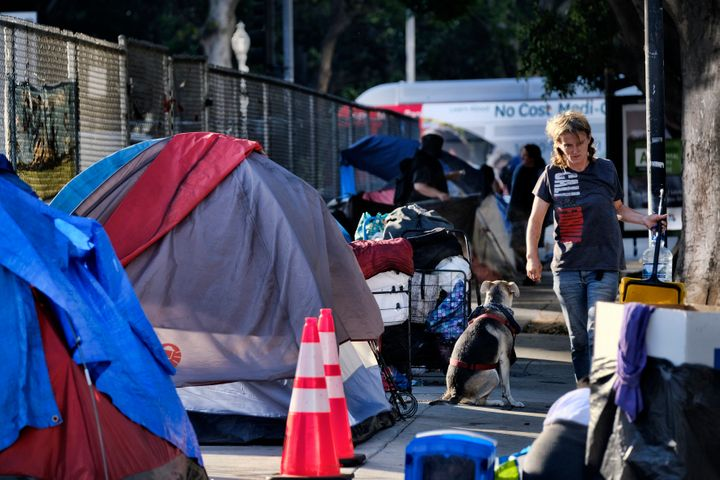 Homeless people move belongings from a street near Los Angeles City Hall as crews prepared to clean the area on Monday, July