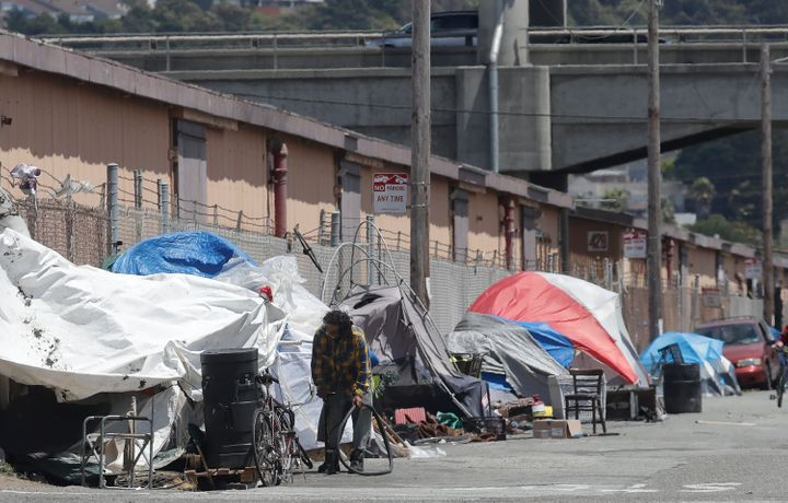 A man holding a bicycle tire outside of a tent along a street in San Francisco on June 27, 2019.
