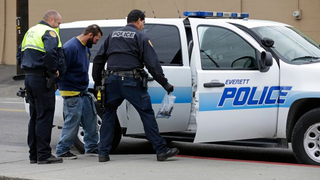 Des officiers de police appréhendent un homme sous le coup d'un mandat d'arrêt...