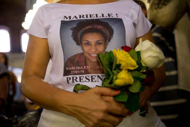 Manifestante veste camiseta e leva flores em protesto quando a morte da ativista completou um ano, em...