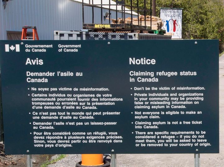 A sign warning asylum seekers is seen at the Canada-U.S. border at Roxham Road on May 9, 2018 in Champlain,NY.