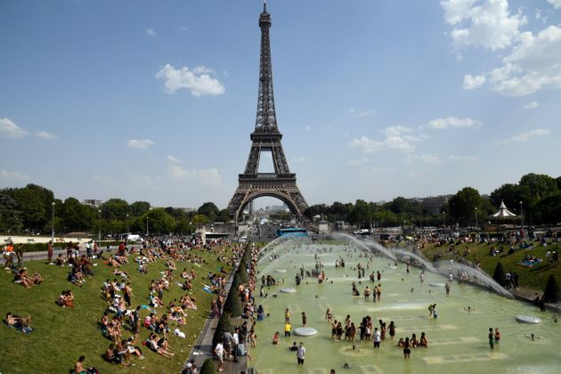 People cool off and sunbathe by the Trocadero Fountains next to the Eiffel Tower in Paris, on July 25,...