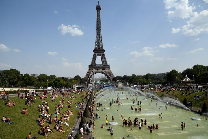 People cool off and sunbathe by the Trocadero Fountains next to the Eiffel Tower in Paris, on July 25, 2019 as a new heatwave