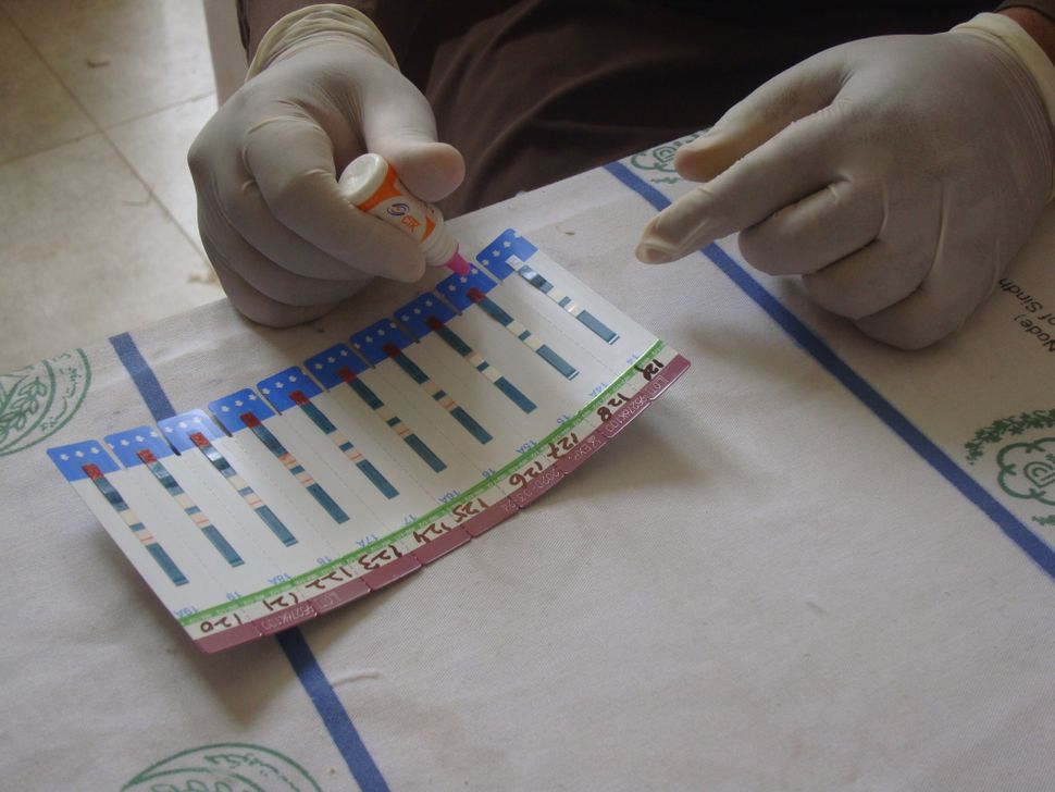 <i>A health technician administers an HIV test. </i>