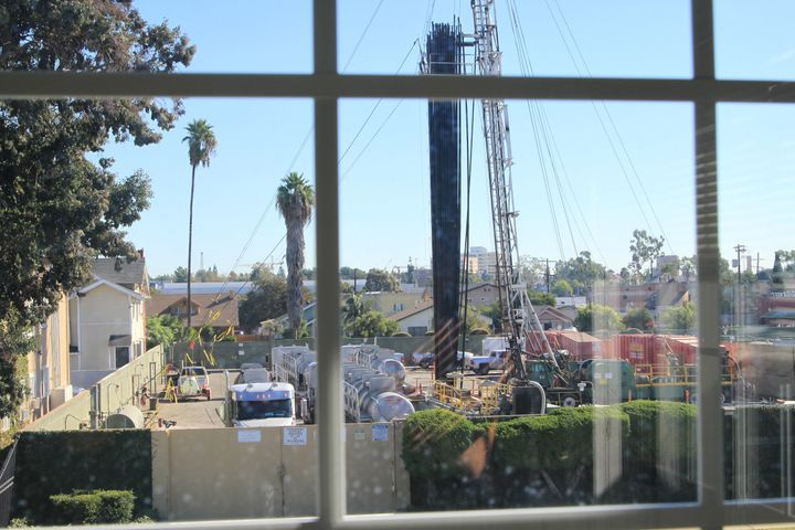 The Jefferson Boulevard drill site seen through a window of a neighboring home. In some places, the site is just feet from oc