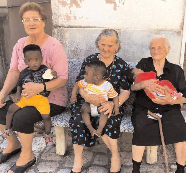 Questo scatto delle nonne di Campoli con i bimbi migranti in braccio mostra il volto