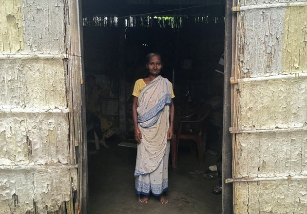 Madhubala Mandal, 59, poses for a photograph inside her bamboo hut in Bishnupur village in