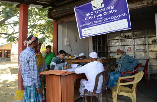 Villagers gather to check their documents at a National Register of Citizens help centre for people whose...