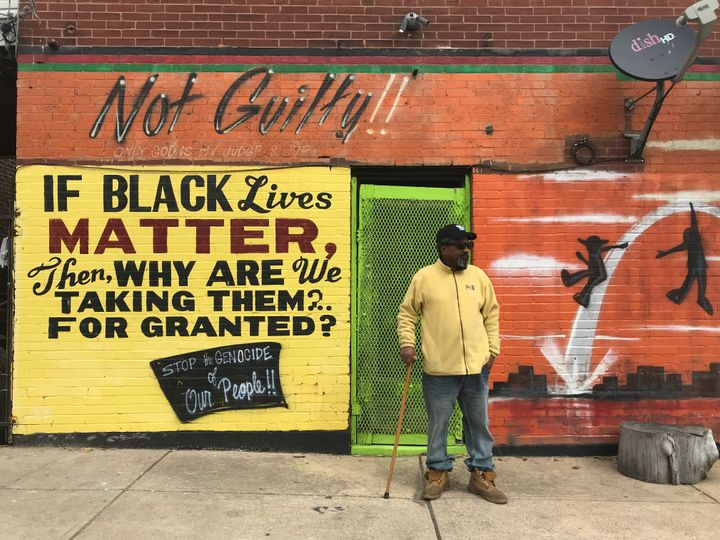 Byron Mischeaux stands in front of his barbecue restaurant in St. Louis. He says he painted these murals after he survived be