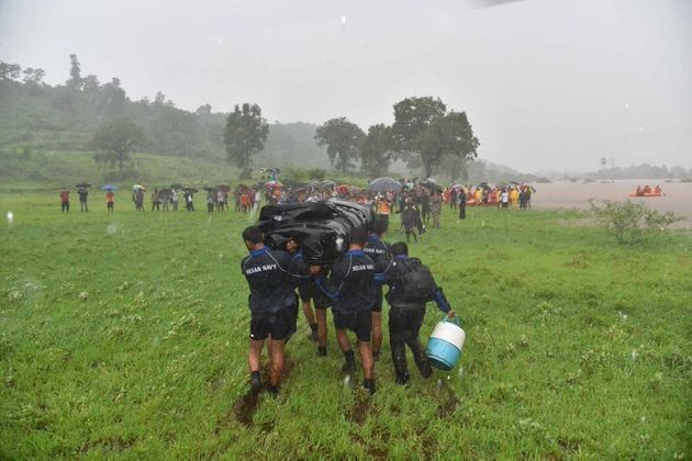 Indian Navy personnel carry boats to the rescue