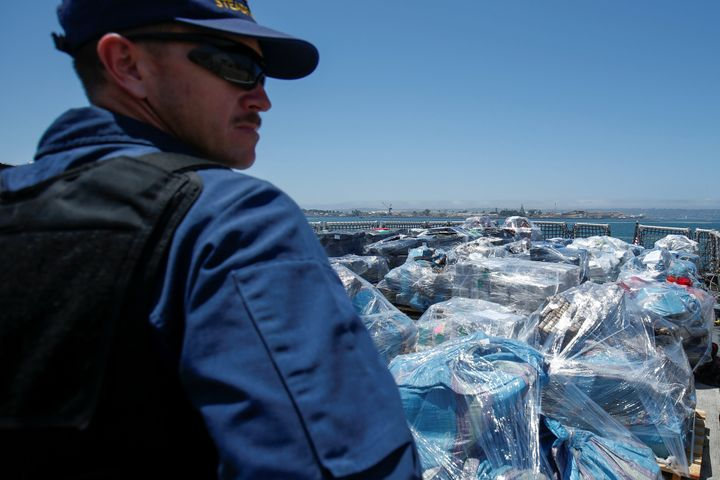 A Coast Guard agent watches over more than 13 tons of cocaine seized off the coasts of Mexico and Central South America befor
