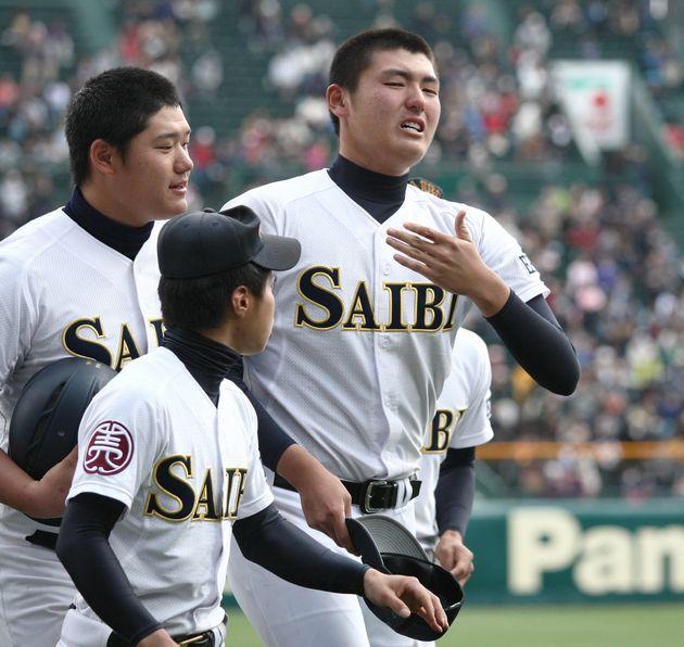 浦和学院に敗れ、応援スタンドにあいさつを終え、ベンチに引き揚げる済美の安楽智大投手(右)=2013年4月3日、甲子園球場