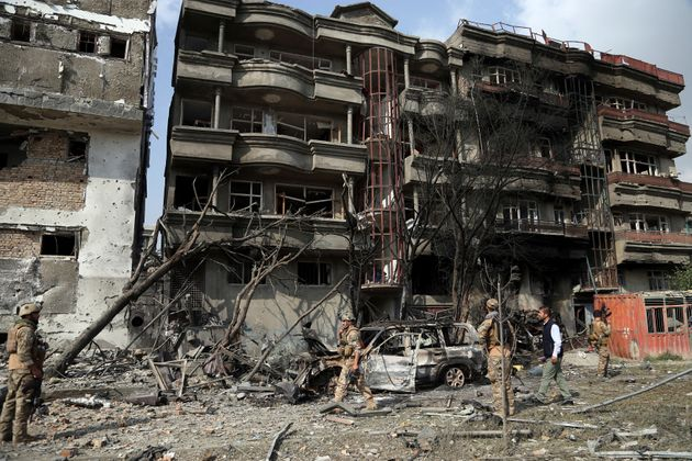Afghan security forces inspect the aftermath of Sunday's attack against the office of the president's...
