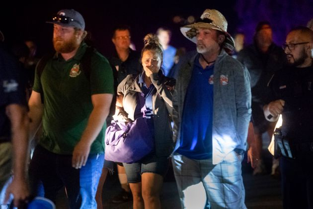 Police officers escort people from Christmas Hill Park following a deadly shooting during the Gilroy...