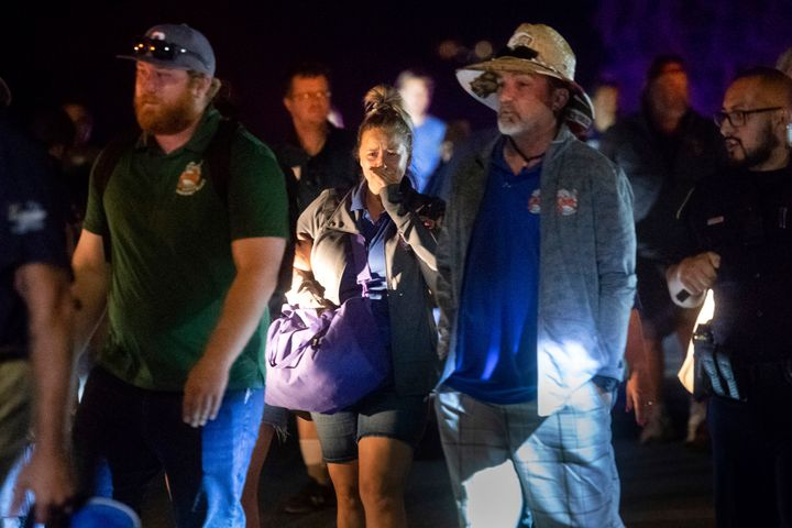 Police officers escort people from Christmas Hill Park following a deadly shooting during the Gilroy Garlic Festival, in Gilr