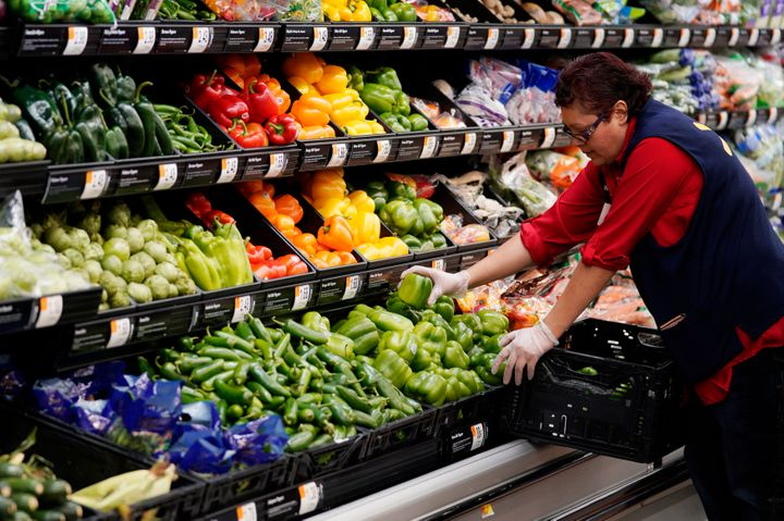 A Walmart worker stocks produce, some of it packaged in single-use plastic.